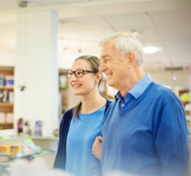 Happy father and daughter standing at pharmacy