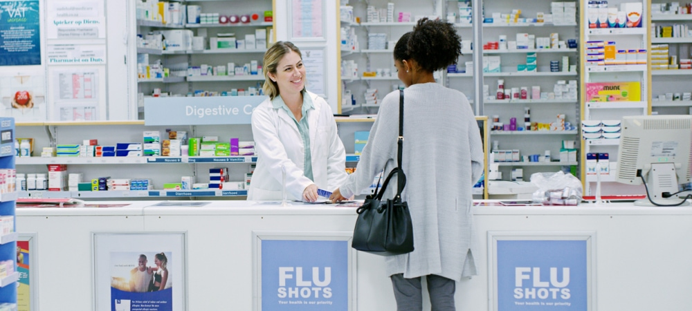 young woman purchasing over the counter medication from a female pharmacist